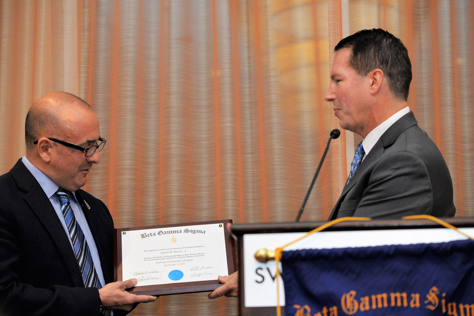 Marketing Associate Professor Rich Rocco hands award to marketing professor Al Muniz at Beta Gamma Sigma induction dinner and ceremony